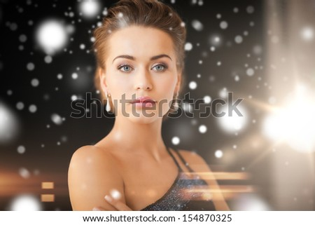 jewelry, luxury, vip, nightlife, party concept - beautiful woman in evening dress wearing diamond earrings - stock photo
