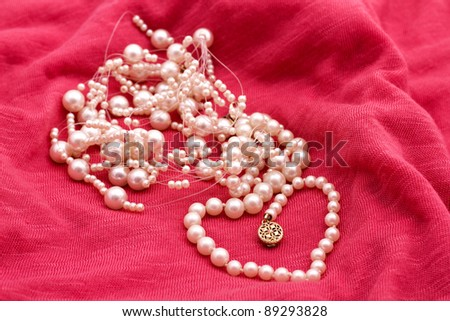 Jewelry made of pearls on the pink background - stock photo