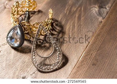 Jewelry on vintage background, beautiful shadow. Oval pendant, earring and golden bracelet on wooden background - stock photo
