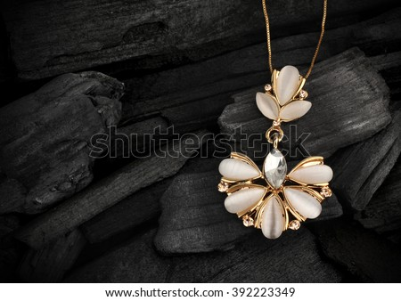 jewelry pendant with gems on darck background - stock photo