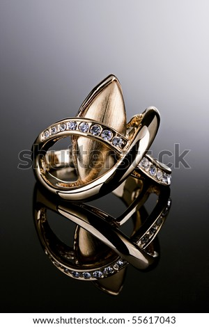 Jewelry photography. Gold ring with diamonds on gradient reflective surface. - stock photo