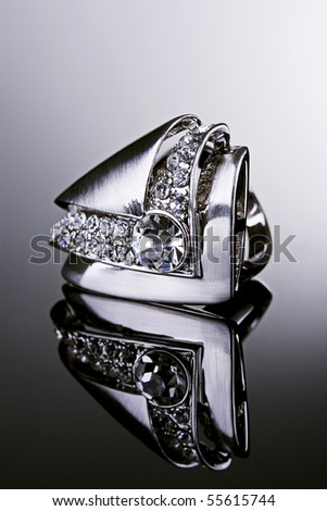 Jewelry photography. Silver ring with diamonds on gradient reflective surface. - stock photo