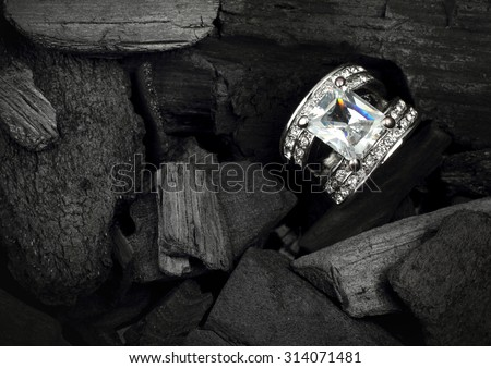 jewelry ring witht big colourful diamond on dark coal background - stock photo