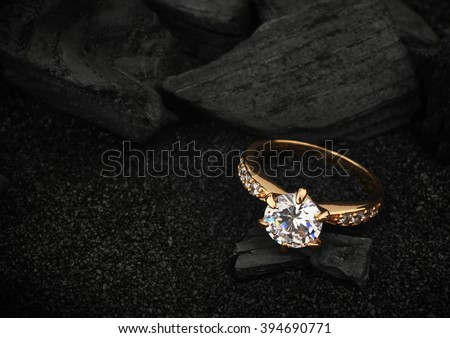 jewelry ring witht big diamond on dark coal and black sand background