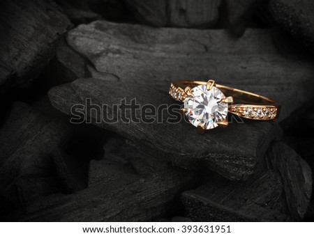 jewelry ring witht big diamond on dark coal background - stock photo