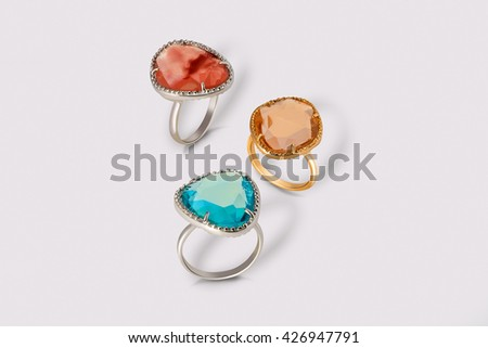 Jewelry set of white and yellow gold rings with colored topazes on grey background.  - stock photo