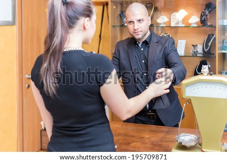 Jewelry store owner is passing a sold product to his buyer, a young woman. - stock photo