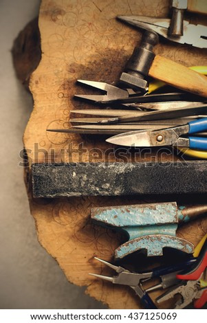 Jewelry tools. Jewellery workplace on wooden background. Top view. Toned image