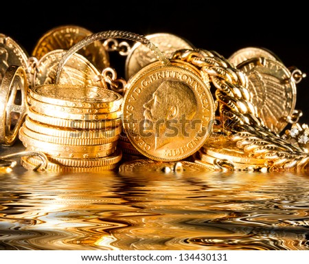 Jewels and gold coins melting  over dark background - stock photo