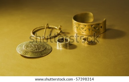 Jewels with ancient Slavic designs on a gold background - stock photo