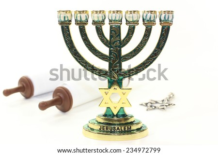Jewish candlestick and Torah scroll in front of white background - stock photo