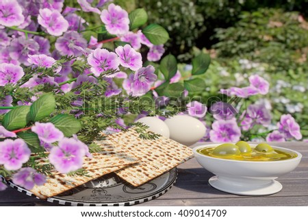Jewish celebrate pesach passover with eggs,olive, matzo and flowers on nature background - stock photo