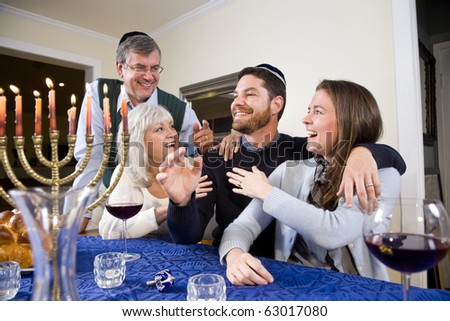 Jewish family celebrating Chanukah at table with menorah - stock photo