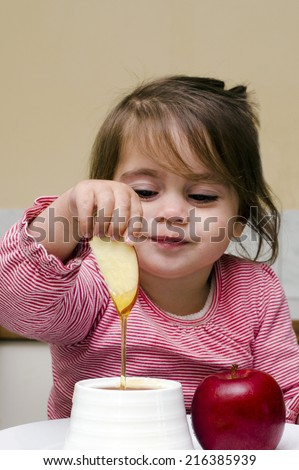 Jewish girl dipping apple slices into honey on Rosh HaShanah the Jewish New Year. - stock photo