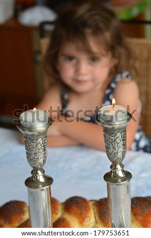 Jewish girl looks at lit sabbath candles before shabbat eve dinner. - stock photo