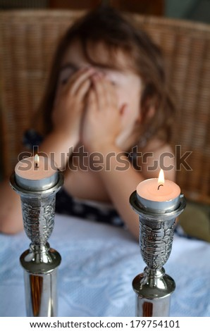 Jewish girl says the blessing upon lighting the sabbath candles before shabbat eve dinner. - stock photo