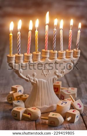 Jewish holiday hannukah symbols - menorah and wooden dreidels - stock photo
