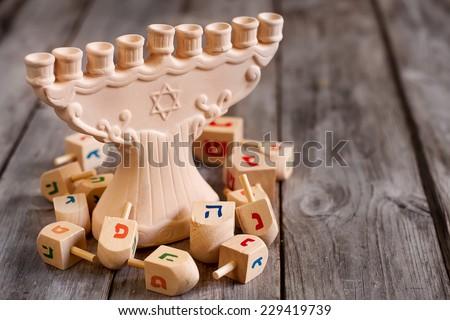 Jewish holiday hannukah symbols - menorah and wooden dreidels. Copy space background. - stock photo