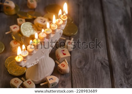 Jewish holiday hannukah symbols - menorah, chocolate coins and wooden dreidels. Copy space background. - stock photo