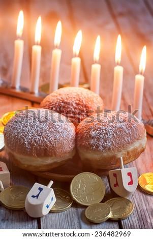 Jewish holiday hannukah symbols - menorah, donuts, chockolate coins and wooden dreidels. - stock photo