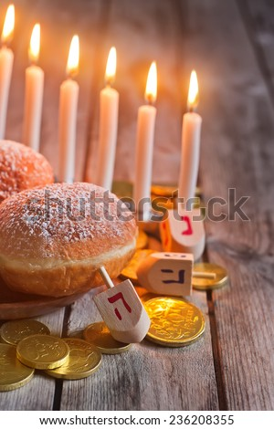 Jewish holiday hannukah symbols - menorah, donuts, chocolate coins and wooden dreidels. Copy space background. - stock photo