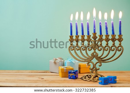 "Jewish holiday Hanukkah background with vintage menorah and gift boxes on wooden table. The Hebrew letters are the first letters of the words ""A great miracle happened here."" - stock photo"