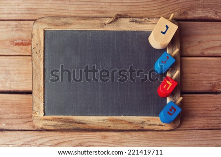 Jewish Holiday Hanukkah background with wooden dreidel spinning top and chalkboard - stock photo