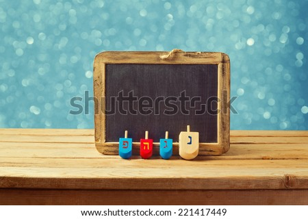 Jewish Holiday Hanukkah background with wooden dreidel spinning top and chalkboard over blue bokeh lights - stock photo