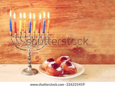 jewish holiday Hanukkah with menorah, doughnuts over wooden table  - stock photo