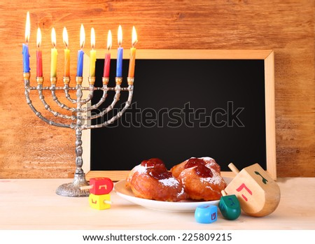 jewish holiday Hanukkah with menorah, doughnuts over wooden table. retro filtered image  - stock photo