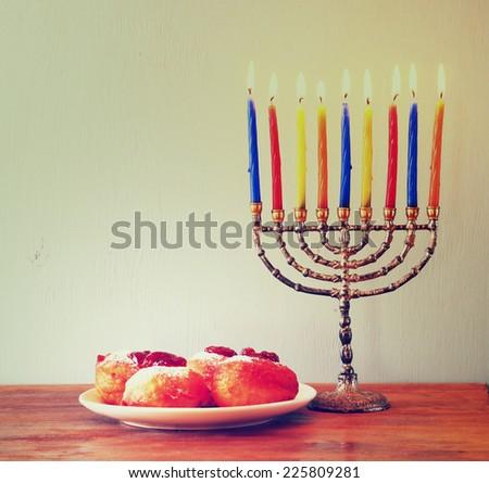 jewish holiday Hanukkah with menorah, doughnuts over wooden table. retro filtered image  - stock photo