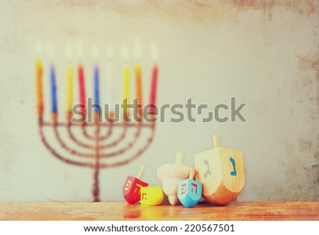 jewish holiday Hanukkah with menorah with wooden dreidels (spinning top). textured and filtered image - stock photo