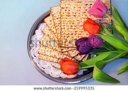 jewish holiday of Passover and its attributes, with matzo and spring tulips - Happy Passover - stock photo