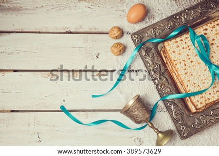 Jewish holiday Passover background with matzoh on wooden white table. View from above.