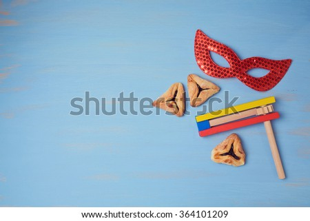 Jewish holiday purim background with carnival mask and  hamantaschen cookies. View from above - stock photo