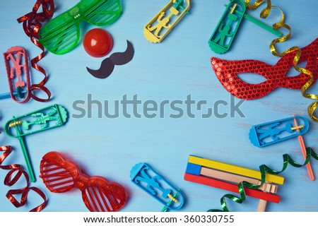 Jewish holiday purim background with carnival mask, party costume and noisemaker. View from above - stock photo