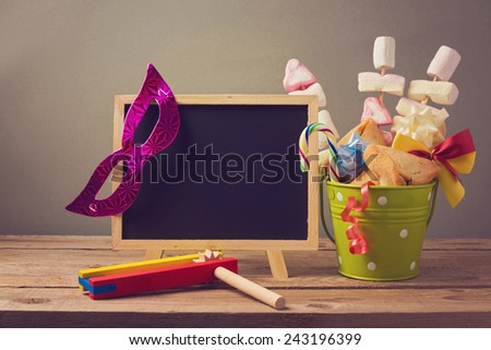 Jewish holiday purim background with chalkboard and gifts - stock photo