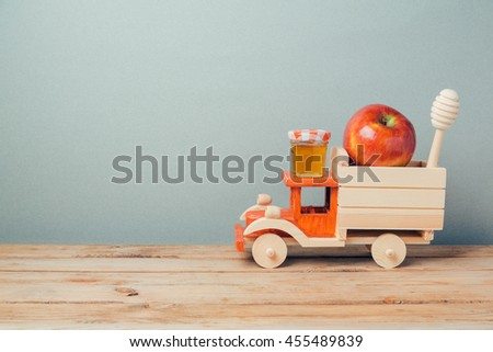 Jewish holiday Rosh Hashana background with toy truck, honey and apples on wooden table