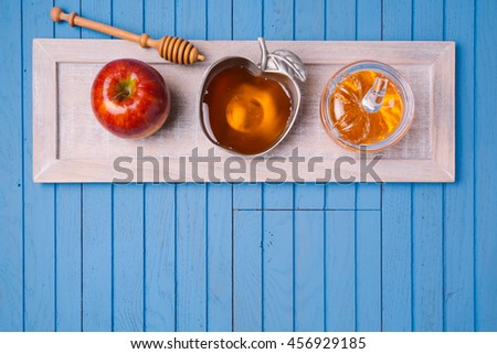 Jewish holiday Rosh Hashana still life with honey and apples on wooden blue table. View from above. Flat lay