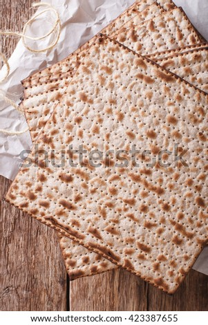 Jewish kosher matzo for Passover macro on a wooden table. vertical view from above - stock photo