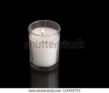 Jewish memorial light. A custom in Judaism is to kindle a yahrzeit candle on the anniversary of the death of a loved one. This light is traditionally a thick wax candle inside a clear, glass jar. - stock photo