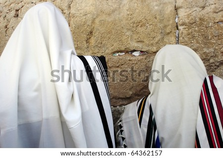 Jewish Men are praying wrapped in talit at the western wall in the old city in Jerusalem, Israel - stock photo