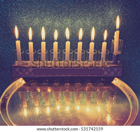 Jewish menorah with candles is traditional symbol for Hanukkah Holiday. Low key image slightly toned for inspiration of retro style