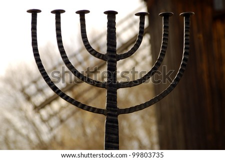 Jewish sign menorah with mill on background - stock photo