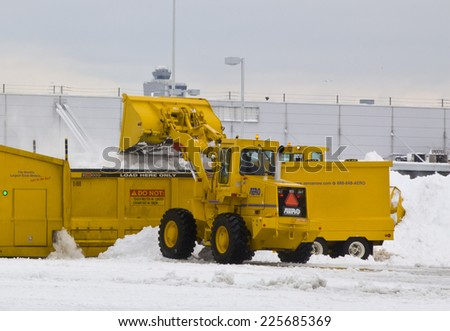 JFK Airport January 2011 Wheel loader machine unloading snow to snow melter with airport work crews after large storm at JFK Airport on January 13, 2011 clearing off taxi ways and run ways. - stock photo