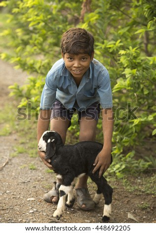 JHALORA, RAJASTHAN, INDIA - JULY 4, 2016: little Garasiya Boy in stable with small lamb. garasiya are an Indian community in the state of Rajasthan