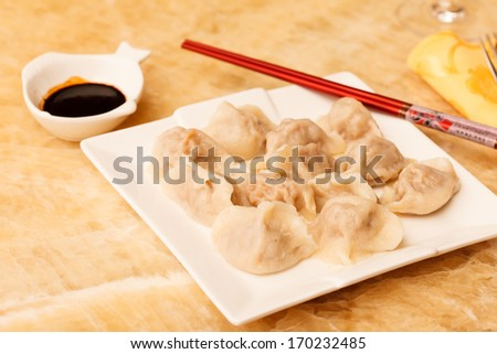 Jiaozi - Chinese dumplings filled with pork and spring onions. - stock photo
