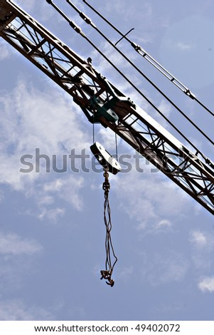 jib crane with cloudy blue sky in the background