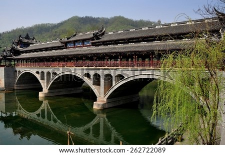 Jie Zi Ancient Town, China - March 6, 2013:  The landmark Ruilong covered bridge with its three broad arches and decorative roofs spans a tranquil river - stock photo
