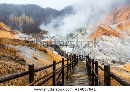 Jigokudani hell valley walking trail in Noboribetsu, Hokkaido, Japan. Selective focus at front banister of wooden footpath.